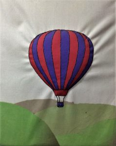 Digital artwork of a hot air balloon decorated with red and blue vertical stripes floating above a green landscape of gently rolling hills.