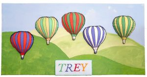 Original artwork by Zoe. Five hot-air balloons digitally printed onto fabric, enhanced with embroidery, padded behind and appliqued onto a painted background of blue sky and rolling green hills. The name Trey has been embroidered onto the bottom of the picture.